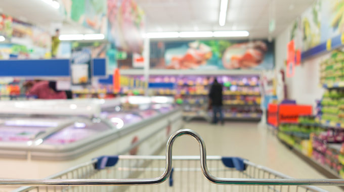 View From Shopping Cart Trolley Basket At Supermarket Self-service Grocery Shop. Retail. Blurred Background.